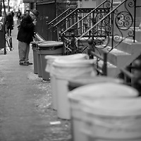 A old man sweeping the sidewalk that is lined with trash cans.