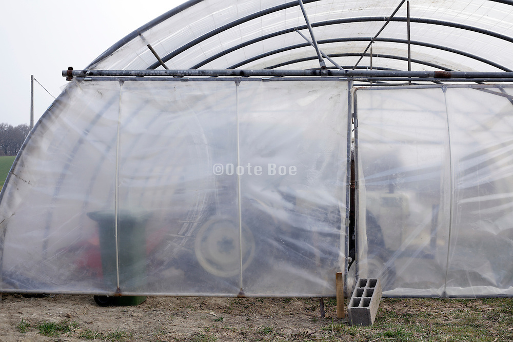 plastic polytunnel greenhouse building with gardening tractor