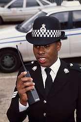 Portrait of community police officer standing in street using walkie talkie,
