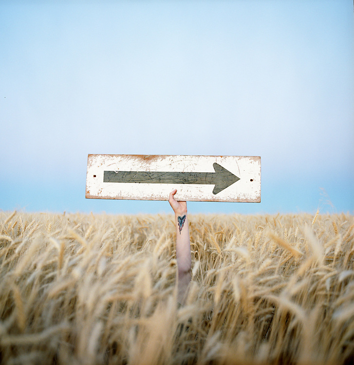 Woman holding arrow sign above a field of wheat in eastern Washington.