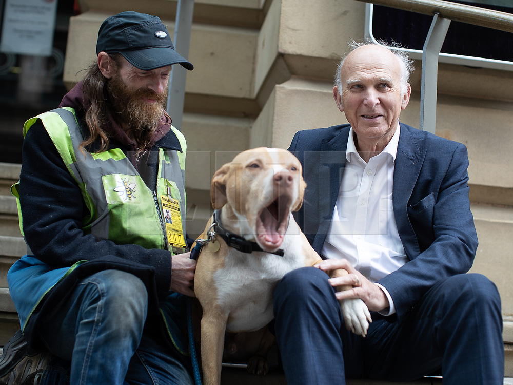 """© Licensed to London News Pictures. 20/06/2019. Manchester, UK. In one of his last actions as Liberal Democrat Party leader , SIR VINCE CABLE meets Big Issue seller JUSTIN GREEN (49) and his dog BUMPER (ten) in Manchester City Centre . The party say they are highlighting what they call a """" Homeless Tax """" , which they oppose , and which could see fines of up to £1,000 imposed upon the homeless by Manchester City Council . The final Local Government Information Unit (LGiU) report from the Local Government Homelessness Commission (LGHC) – a year-long initiative set up to investigate how councils can fulfil their obligation to prevent homelessness - is due to be published . The Liberal Democrats will appoint a new leader in July . Photo credit: Joel Goodman/LNP"""