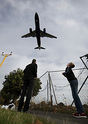 """© Licensed to London News Pictures. 27/10/2016. London, UK. A man and his son stand on the flight path as an airliner comes into land at Heathrow Airport. The government has announced that a third runway will be built at the United Kingdom's busiest airport. The Cabinet are divided - with Foreign Secretary Boris Johnson saying that the project is """"undeliverable"""". Conservative MP for Richmond Zac Goldsmith has resigned. Photo credit: Peter Macdiarmid/LNP"""