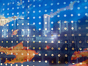 """The Seattle Space Needle and skyline are seen through glass wall art. The """"Seattle Cloud Cover"""" glass bridge art was completed in 2006 by Teresita Fernández (born 1958). Seattle Art Museum's Olympic Sculpture Park opened in 2007 at the southern end of Myrtle Edwards Park. Free entry. Address: 2901 Western Avenue, Seattle, Washington 98121"""