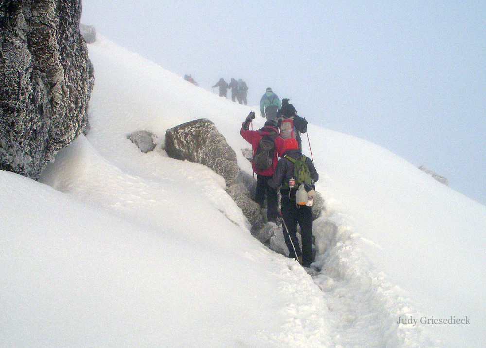The snow deepens and footing is treacherous around the side of the mountain as climbers begin the final push to the summit of Mt. Kilimanjaro at sunrise.