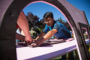 Ken Hu holds a playhouse door as others screw the hinges in place during a Habitat for Humanity playhouse build at the SanDisk headquarters in Milpitas, California, on August 27, 2013. (Stan Olszewski/SOSKIphoto)