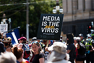"""A """"media is the virus' sign is seen during the Melbourne Freedom Rally at Parliament House. Police move into position on the steps of state parliament ahead of a planed protest. The groups who have organised the many Freedom Day protests over the last 3 months, attempted to march on State Parliament during Melbourne Cup Day demanding the sacking of Premier Daniel Andrews for the lockdown and attacks on their civil liberties. Police met with the protester's with significant force despite the city having had zero cases for five days. (Photo by Dave Hewison/Speed Media)"""