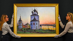 "© Licensed to London News Pictures. 22/11/2019. LONDON, UK. Technicians present ""The Ancient Town of Uglich"", 1913, by Konstantin Yuon (Est. GBP600-900k) at the preview for the upcoming sales of Russian artworks at Sotheby's New Bond Street.  The Russian Pictures and Works of Art, Fabergé and Icons sales take place on 26 November.  Photo credit: Stephen Chung/LNP"