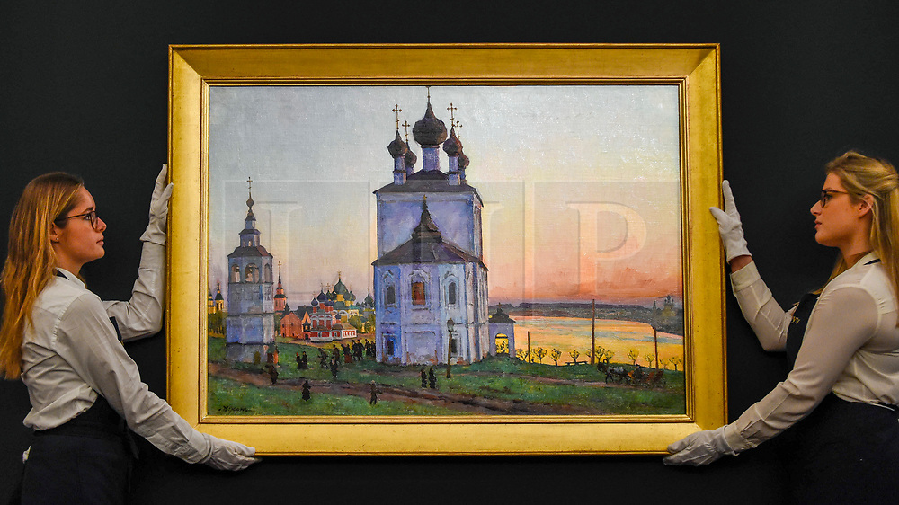 """© Licensed to London News Pictures. 22/11/2019. LONDON, UK. Technicians present """"The Ancient Town of Uglich"""", 1913, by Konstantin Yuon (Est. GBP600-900k) at the preview for the upcoming sales of Russian artworks at Sotheby's New Bond Street.  The Russian Pictures and Works of Art, Fabergé and Icons sales take place on 26 November.  Photo credit: Stephen Chung/LNP"""