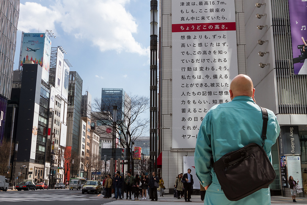 A man looks at a  large billboard on the side of the Sony Building in Ginza marking the sixth anniversary of the March 11th 2011 earthquake and tsunami in Tohoku. Ginza, Tokyo, Japan. Friday March 10th 2017 The billboard was created by Yahoo and asks passersby to remember the disaster and the nearly 16,000 people who died. The line marked in red shows the maximum height of the tsunami (16.7 metres at Ofunato in Miyagi prefecture. The billboard is on display until March 12th.