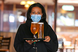 © Licensed to London News Pictures. 16/05/2021. London, UK. A staff member with glasses of beer at The Toll Gate - JD Wetherspoon pub in north London. On Monday 17 May, pubs and restaurants will welcome back customers indoors for the first time in more than five months, as Covid-19 restrictions are eased. Photo credit: Dinendra Haria/LNP