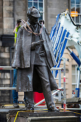 The sculpture of Sherlock Holmes by former pop-artist Gerald Laing is being moved from it's home on Picardy Place, yards from the birth place of Sir Arthur Conan Doyle.<br /> <br /> The move of the sculpture is to accommodate road and tram works that are taking place in Edinburgh. The statue will be moved to Nairn at  Black Isle Bronze Ltd by the artists son, Farquhar Laing where it will stay for two years until it returns to Edinburgh.<br /> <br /> Pictured: The first of the lifting straps is passed around Sherlock Holmes neck