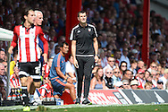 Marinus Dijkhuizen, the Brentford head coach (c) looks on from the touchline. Skybet football league Championship match, Brentford v Ipswich Town at Griffin Park in London on Saturday 8th August 2015.<br /> pic by John Patrick Fletcher, Andrew Orchard sports photography.