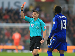 Referee Craig Pawson shows Leicester City's Jamie Vardy (out of picture) a red card