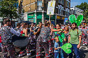 Members of the Batala drum band from Brazil stop playing and hug residents who ask acts to honour a quiet zone to remember the Grenfell Tower tragedy - The Monday of the Notting Hill Carnival. The annual event on the streets of the Royal Borough of Kensington and Chelsea, over the August bank holiday weekend. It is led by members of the British West Indian community, and attracts around one million people annually, making it one of the world's largest street festivals.