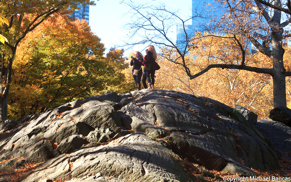 Thee young women talking photos while walking in the fall in Manhattan's Central Park.