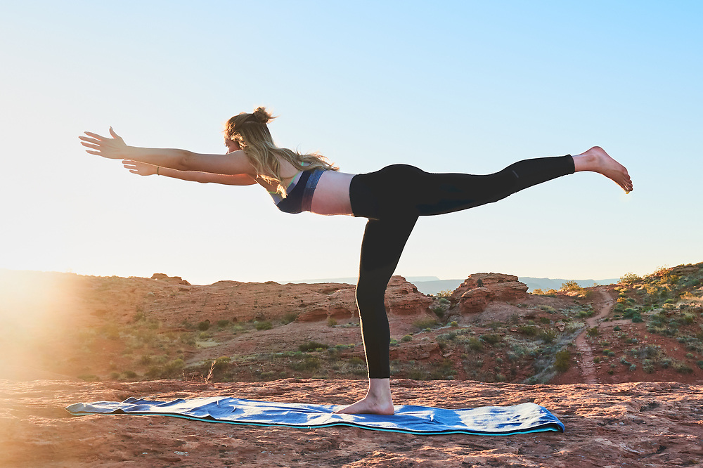 Female doing yoga at sunrise in the red rocks of beautiful southern Utah.