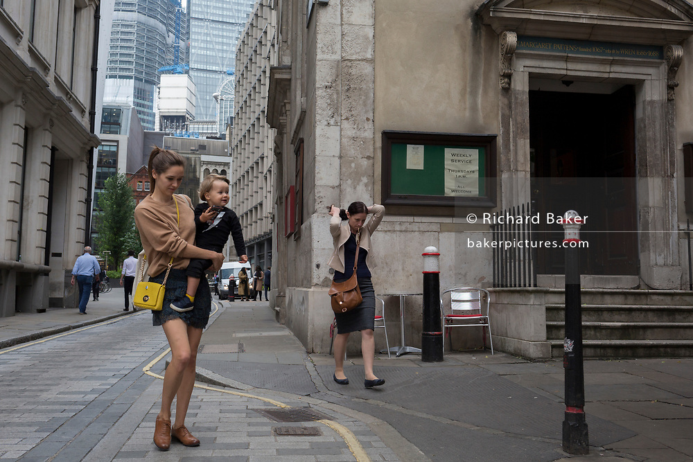 Women walk through a narrow street alongside St Margaret Pattens church, on the corner of Rood Lane and Eastcheap, in the City of London, the capital's financial district, on 4th June 2018, in London, England.