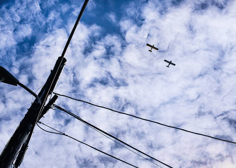 """Two airplanes fly overhead, in a windswept cloudy blue sky, framed by powerlines 