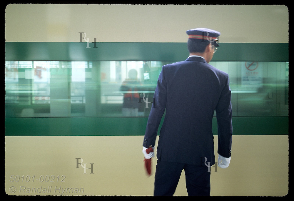 Green & yellow stripes of bullet train frame stationmaster as train rushes out of Utsunomiya. Japan