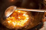 Cooking tofu in deep fat in a wok at a small restaurant in Zhongdian also known as Shangrila, Yunnan province, China.