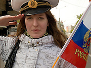 Junge Frau mit der russischen Nationalflagge und dem russischen Wappen im Zentrum salutiert vor der groessten Militaerparade in Russland seit Ende der Sowjetunion 1991 (9.Mai 2008).<br /> <br /> Young women with the Russian flag saluting shortly before the Victory Day parade (took place the 9th of May 2008) which showcased military hardware for the first time since the Soviet collapse.