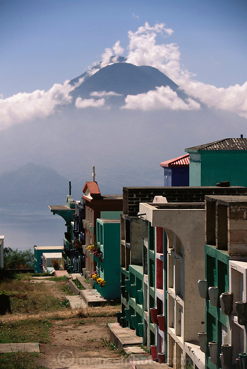 Above-ground graves in a cemetery overlooking Lake Aititlan in Solola, Guatemala with volcanoes in the distance.
