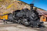 The train engine & cars depart Silverton, Colorado, USA. The Durango and Silverton Narrow Gauge Railroad, a National Historic Landmark, links Durango to Silverton, in Colorado, USA. Silverton is a former silver mining camp, now the federally-designated Silverton Historic District. Silverton no longer has active mining, but subsists on tourism, maintenance of US 550 (which links Montrose with Durango), mine pollution remediation, and retirees.
