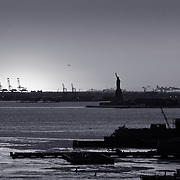 Statue of Liberty and factories in the setting sun.