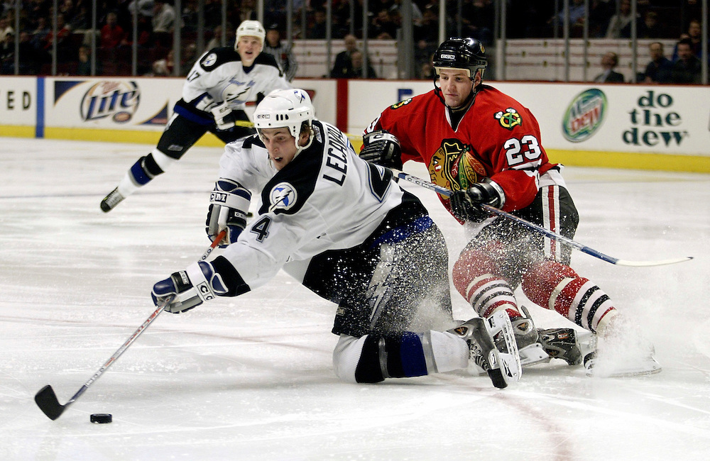 The Chicago Blackhawks' Jim Vandermeer, left, takes a shot as he is brought down by the Tampa Bay Lightning's Vincent Lecavalier.