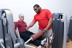 Fitness instructor showing an older man how to use the leg curl machine at his sports leisure centre,