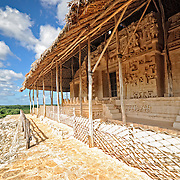 "Ornate carvings on the exterior of the Tomb of Ukit Kan Le'k Tok' at the ancient Mayan ruins at Ek'Balam, near Valladolid, Yucatan, Mexico. The jaguar is a recurring motif, as evidenced by the large stone teeth, etc. Ek' Balam means ""dark jaguar."" The Acropolis towers above the surrounding countryside."