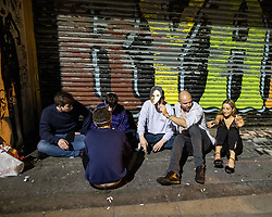 © Licensed to London News Pictures . 28/10/2018. Manchester, UK. People sit on the pavement outside a club in the Northern Quarter of Manchester City Centre . Revellers on a night out , many in fancy dress , on the weekend before Halloween . Photo credit: Joel Goodman/LNP