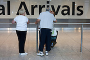 Emotional greeeting after long absence in International Arrivals concourse at Heathrow's terminal 5.