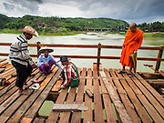 16 SEPTEMBER 2014 - SANGKHLA BURI, KANCHANABURI, THAILAND: A Buddhist monk from the Mon community in Sangkhla Buri talks to workers helping repair the Mon Bridge. The 2800 foot long (850 meters) Saphan Mon (Mon Bridge) spans the Song Kalia River. It is reportedly second longest wooden bridge in the world. The bridge was severely damaged during heavy rainfall in July 2013 when its 230 foot middle section  (70 meters) collapsed during flooding. Officially known as Uttamanusorn Bridge, the bridge has been used by people in Sangkhla Buri (also known as Sangkhlaburi) for 20 years. The bridge was was conceived by Luang Pho Uttama, the late abbot of of Wat Wang Wiwekaram, and was built by hand by Mon refugees from Myanmar (then Burma). The wooden bridge is one of the leading tourist attractions in Kanchanaburi province. The loss of the bridge has hurt the economy of the Mon community opposite Sangkhla Buri. The repair has taken far longer than expected. Thai Prime Minister General Prayuth Chan-ocha ordered an engineer unit of the Royal Thai Army to help the local Mon population repair the bridge. Local people said they hope the bridge is repaired by the end November, which is when the tourist season starts.    PHOTO BY JACK KURTZ