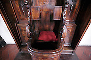 close up of an ornate open confessional with red cushion for the priest