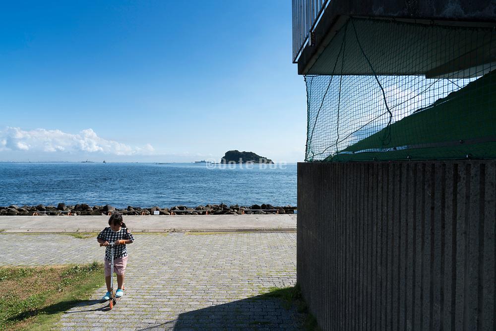 child with push scooter at Umikaze park, Yokosuka with Tokyo Bay and Sarushima Island
