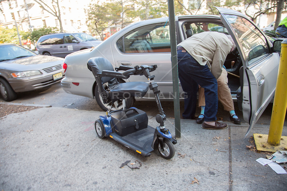 man helping a woman into a car from a motorized wheel chair in New York City