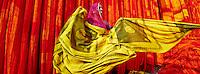 Inde, Rajasthan, Usine de Sari, Sita Devi, 40 ans. Les tissus sechent en plein air. Ramassage des tissus secs par des femmes et des enfants avant le repassage. Les tissus pendent sur des barres de bambou. Les rouleaux de tissus mesurent environ 800 m de long. <br />  // India, Rajasthan, Sari Factory, Sita Devi, 40 old. Textile are dried in the open air. Collecting of dry textile  are folded by women and children. The textiles are hung to dry on bamboo rods. The long bands of textiles are about 800 metre in length.
