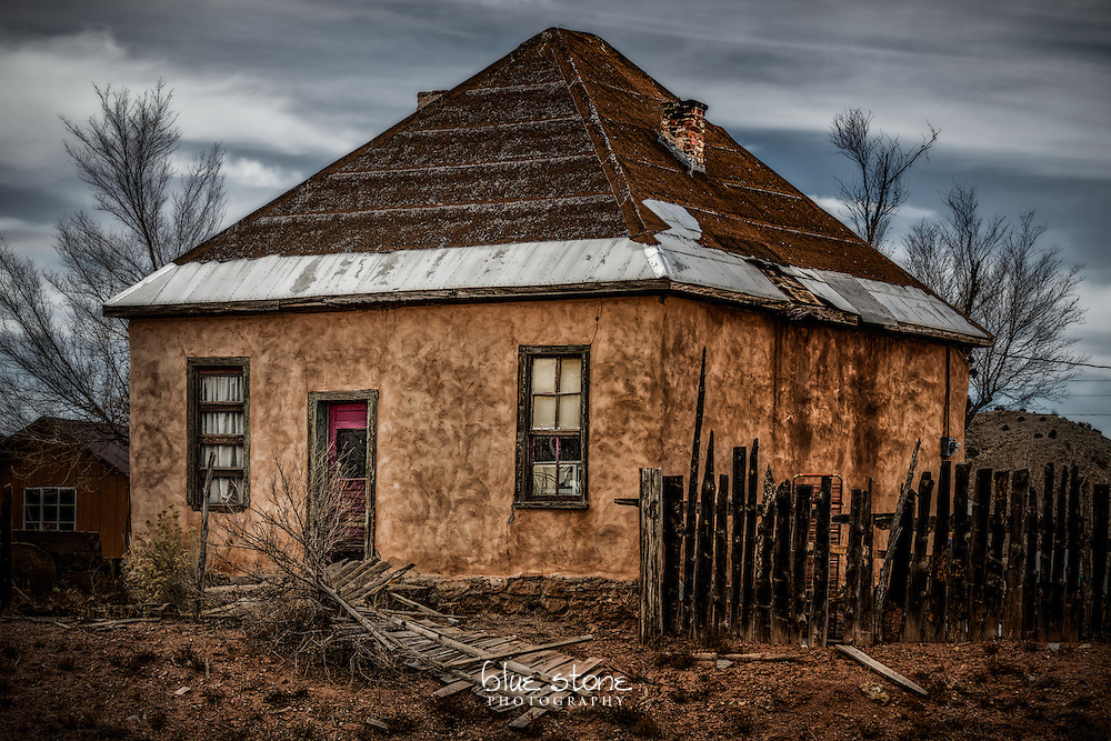 An aged adobe house that is in disrepair with a broken wood fence, faded red door and missing shingles on the roof shows that one's home is a castle<br /> <br /> Wall art is available in metal, canvas, float wrap and standout. Art prints are available in lustre, glossy, matte and metallic finishes.