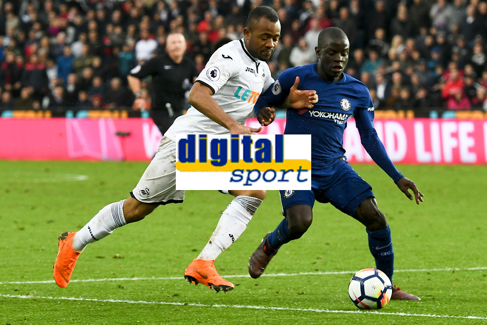 Football - 2017 / 2018 Premier League - Swansea City vs. Chelsea<br /> <br /> Jordan Ayew of Swansea City & N'Golo Kanté of Chelsea contest the ball,, arm in arm,  at the Liberty Stadium.<br /> <br /> <br /> COLORSPORT/WINSTON BYNORTH