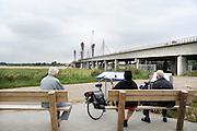 Nederland, Ewijk, 31-7-2012Wegverbreding van de A50 tussen de knooppunten Ewijk en Valburg. Onderdeel van deze wegverbreding is de bouw van een extra brug over Waal. De laatste brug van deze omvang die Rijkswaterstaat realiseerde, was de Martinus Nijhoffbrug over de Waal bij Zaltbommel in 1995. Mensen, ouderen, bij een bord met informatie over de constructie van deze oeververbinding. Drie oudere fietsers rusten op een bankje uit.Foto: Flip Franssen/Hollandse Hoogte