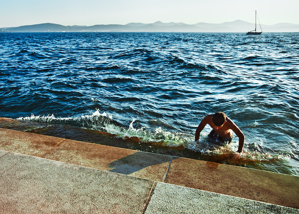 A swimmer getting out of the water at the steps of the Sea Organ in Zadar, Croatia. Designed by architect Nikola Basic, 35 organ pipes are built under the steps so that the wind and water from the sea create musical sounds.