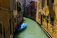 A boat moored in a sunlit section of canal, Venice, Italy