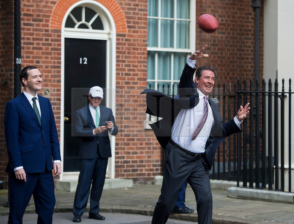 © Licensed to London News Pictures. 02/10/2015. London, UK. British chancellor GEORGE OSBORNE watches DAN MARNO (right) and Curtis Martin (not pictured) throwing an american football after meeting with NFL team owners, execs and former stars at Downing Street ahead of this weekend NFL game at Wembley stadium.  Photo credit: Ben Cawthra/LNP