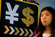 HONG KONG, MAY 08: A person stands next to a sign displaying symbols of the Hong Kong dollar and the Chinese yuan (RMB), on May 8, 2015, in Hong Kong. (Photo by Lucas Schifres/Pictobank)