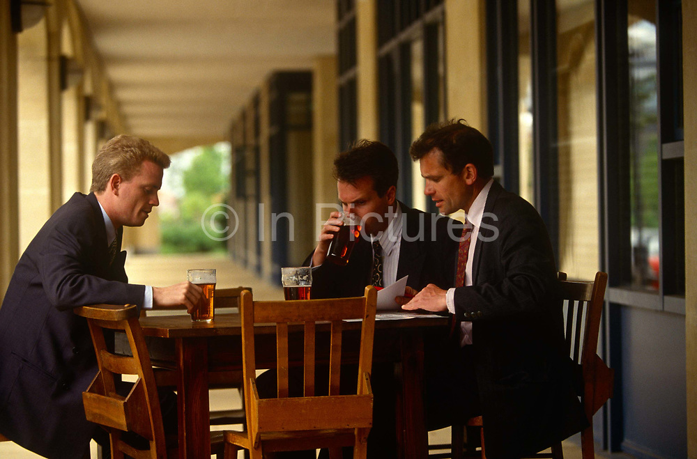 Three businessmen gather for an informal meeting, outside a bar in central Milton Keynes, UK. Each with a pint of bitter or lager, the three associates sit outside a bar in the town centre at lunchtime, half-way through the working day. One takes a sip from his pint glass and the others refer to paperwork, the subject of their time together.
