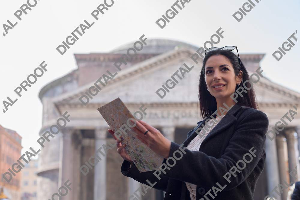 Happy and smiling tourist woman hold  a map at the Pantheon in Rome Italy and smile