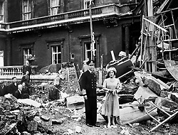 File photo dated 10/09/40 of King George VI and the Queen Mother standing amid the bomb damage at Buckingham Palace. A teenage Princess Elizabeth danced in jubilation on VE Day after slipping into the crowds unnoticed outside Buckingham Palace.