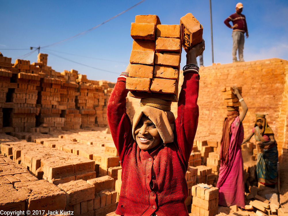 03 MARCH 2017 - BAGMATI, NEPAL: A woman balances finished bricks on her head to carry them to a truck at a brick factory in Bagmati, near Bhaktapur. There are almost 50 brick factories in the valley near Bagmati. The brick makers are very busy making bricks for the reconstruction of Kathmandu, Bhaktapur and other cities in the Kathmandu valley that were badly damaged by the 2015 Nepal Earthquake. The brick factories have been in the Bagmati area for centuries because the local clay is a popular raw material for the bricks. Most of the workers in the brick factories are migrant workers from southern Nepal.       PHOTO BY JACK KURTZ