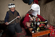 A young Kyrgyz boy named Ker-u Din is playing while his mum sewing..The Kyrgyz settlement of Tchelab, near Chaqmaqtin lake, Haji Bootoo Boi's camp...Trekking through the high altitude plateau of the Little Pamir mountains, where the Afghan Kyrgyz community live all year, on the borders of China, Tajikistan and Pakistan.